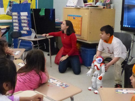An example of  the robotics curriculum for higher functioning special education students discussed on Better Together is demonstrated above with ESCNJ Teacher Naomi Glassman (red sweater), working with students who  programmed a robot to read a Dr. Seuss book for Read Across America.