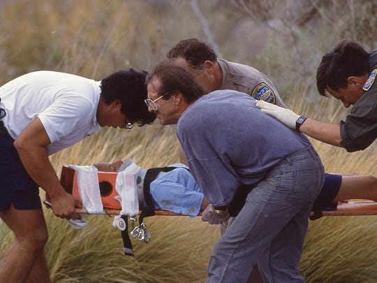 Palm Springs Mayor Sonny Bono (blue shirt) helps carry an injured Girl Scout, Tracie Schiebel of San Antonio, to a waiting helicopter at the site of the Girl Scouts bus crash on Tramway Road on July 31, 1991.