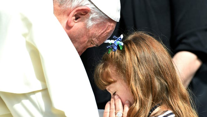 Pope Francis embraces five-year-old Lizzy Myers from the United States who suffers from a rare genetic disease which will take away her hearing and gradually make her blind.