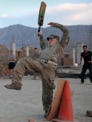 Iowa National Guard Alpha Company 1-133rd Battalion SPC Curtis Blake dodges a cricket ball while playing with the Afghan locals in 2011.