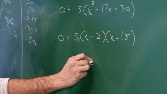 A teacher writes algebraic equations on a classroom chalkboard. /Charlie Nye / The Star 2003 file photo