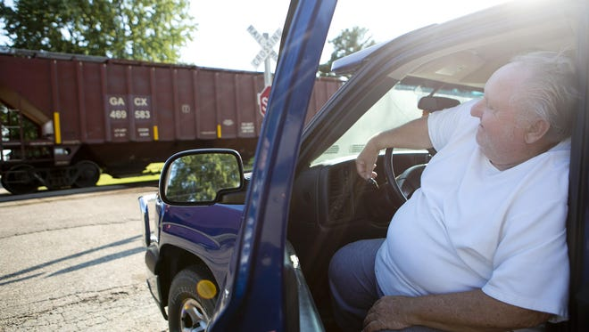 Bob Weinfurter, who passed away in December, waits in his truck for the train to move in Auburndale in this file photo. Weinfurter had been in his car for four hours at that point waiting for the train to move which cut off access to homes and Auburndale's recycling plant. His widow, Linda, said she and her husband used to worry about what would happen if he needed an ambulance and the train was blocking their street.