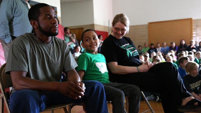 Trayson Harrell, middle, looks at his dad, Eric Harrell, as his mom, Amy smiles at him during a school assembly at Lincoln Elementary to welcome him back to school Monday.
