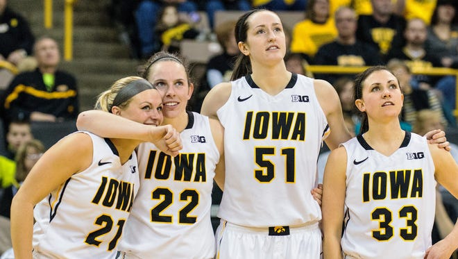 Iowa seniors Melissa Dixon (21), Samantha Logic (22), Bethany Doolittle (51) and Kathryn Reynolds (33) watch a tribute video during post-game festivities on senior day at Carver-Hawkeye Arena in Iowa City on Sunday, March 1, 2015. The Hawkeyes beat the Gophers 92-76.