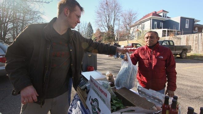 Bruce Ucán, chef at The Mayan Cafe, right, with Colter Hubsch of Wild Carrot Farm, left, at the Bardstown Road Farmers Market in Louisville, KY. Mar. 28, 2015