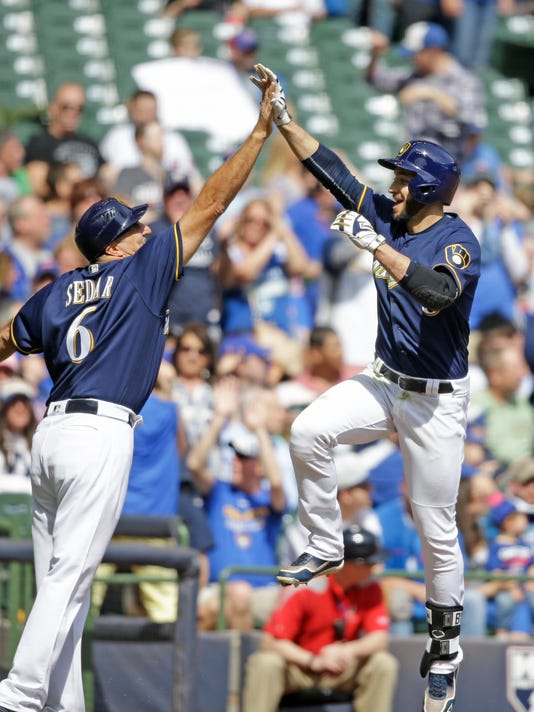 Milwaukee Brewers' Ryan Braun, right, gets a high-five from third base coach Ed Sedar after Braun's three-run home run against the Chicago Cubs during the third inning of a baseball game Sunday, April 9, 2017, in Milwaukee. (AP Photo/Jeffrey Phelps)