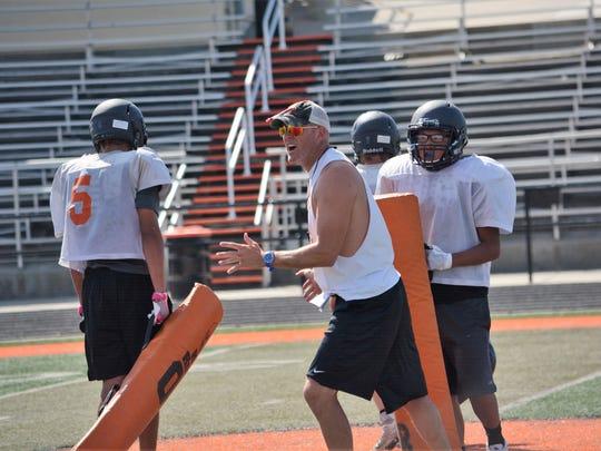 Aztec coach Matthew Steinfeldt explains a blocking drill during Tigers football practice on Thursday, August 10.
