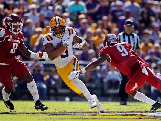LSU running back Derrius Guice (5)carries between Arkansas linebacker De'Jon Harris (8) and defensive back Santos Ramirez (9) in the first half of an NCAA college football game in Baton Rouge, La., Saturday, Nov. 11, 2017. (AP Photo/Gerald Herbert)