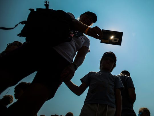 Eclipse watchers use a pin hole in a card to project