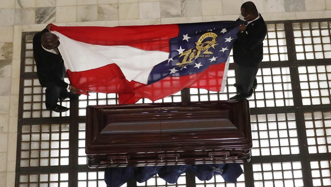 The Georgia state flag is prepared to lie on the casket of The Rev. C.T. Vivian in the capitol rotunda during his memorial service, Wednesday, July 22, 2020, in Atlanta. Rev. Vivian, an early and key adviser to the Rev. Martin Luther King Jr. who organized pivotal civil rights campaigns and spent decades advocating for justice and equality, died Friday at the age of 95.