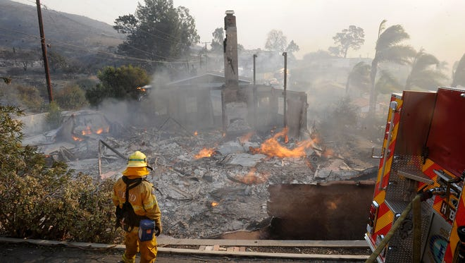 A firefighter sprays down a smoldering home in a Ventura, Calif., hillside neighborhood Tuesday, Dec. 5, 2017, as the Thomas Fire burned at least 55,000 acres, or 85.9 square miles, between Santa Paula, Calif., and Ventura.