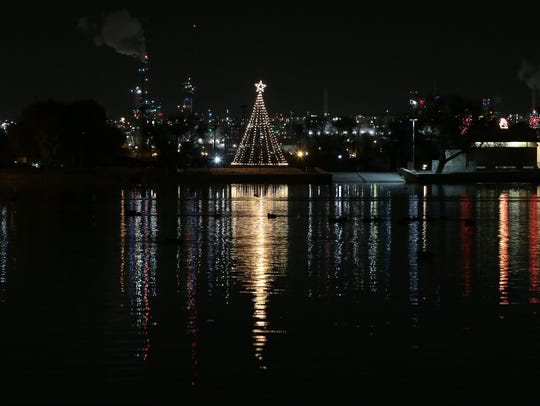 A Christmas tree is reflected in the water Sunday at
