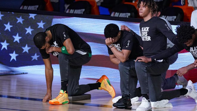 Celtics forward Jayson Tatum, left, takes a knee with teammates during the national anthems before the conference semifinal playoff game against the Toronto Raptors Wednesday evening in Lake Buena Vista, Fla.