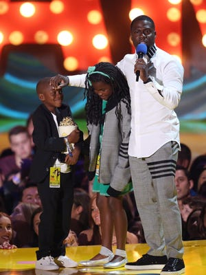 Kevin Hart, right, appears on stage with his kids Hendrix Hart, left, and Heaven Hart as he accepts the comedic genius award at the MTV Movie Awards at the Nokia Theatre on Sunday, April 12, 2015, in Los Angeles. (Photo by Matt Sayles/Invision/AP) ORG XMIT: CACJ217