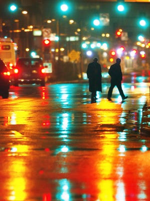 After the rain, pedestrians are illuminated by signal lights as they cross Central Avenue in downtown Phoenix Dec. 22, 2008.