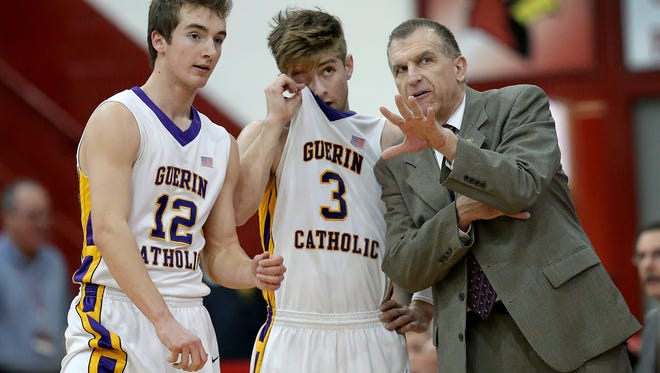 Guerin Catholic coach Pete Smith, right, talks with Cameron Lindley (3) and Matthew Godfrey (12). The Golden Eagles play Griffith in Saturday's 3A title game.