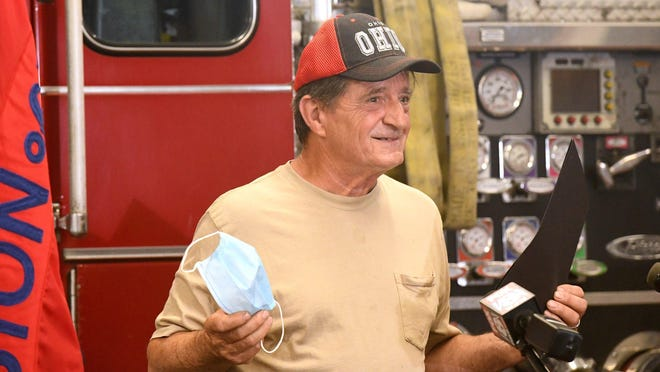Norman Yoder, who used his ladder to help four people flee a burning house at 915 Smith Ave. S.W. on July 15, receives a Good Samaritan award from the Canton Fire Department at Canton Fire Station 1 on  Monday.