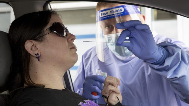 Registered nurse Keith M. takes a sample from Sharon at a drive-through COVID-19 test site at Austin Emergency Center on South Lamar Boulevard. A CDC study found that people who test positive still have symptoms weeks to months later.
