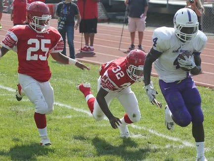 New Rochelle's Keelan Thomas scores a first half touchdown as North Rockland's Michael Cintron and Cameron Lewis follow, during action in their game at North Rockland High School, Sept. 19, 2015.