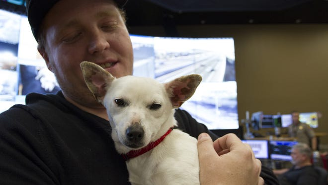 Jayson Winter, an Arizona Department of Transportation supervisor, holds a puppy at the ADOT office building on Jan. 26, 2016 in Phoenix, Ariz. The dog stayed the night before with winter after it was found sitting on a median on State Route 51 alongside traffic.
