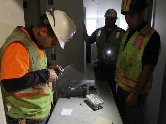 Contractors Joshua Vandergrift works on splicing a