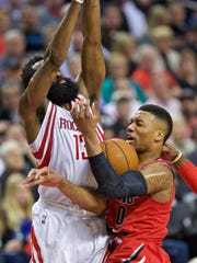 Portland Trail Blazers guard Damian Lillard, right, is fouled by Houston Rockets guard James Harden during the second half of an NBA basketball game in Portland, Ore., Thursday, Feb. 25, 2016. (AP Photo/Craig Mitchelldyer)