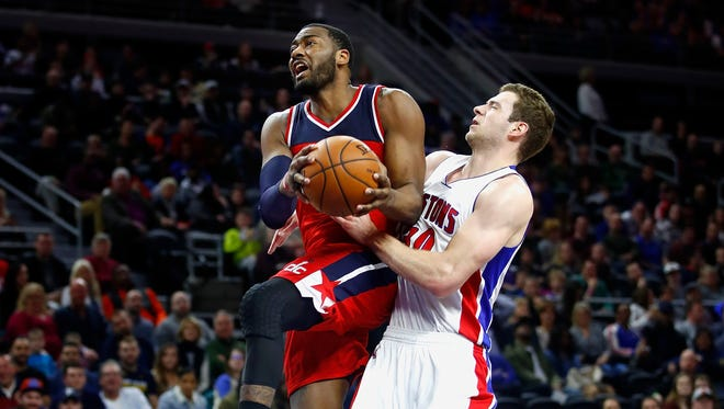 Wizards guard John Wall tries to get off a shot while being defended by Pistons forward Jon Leuer during the Pistons' 113-112 win over the Wizards on Jan. 21, 2017 at the Palace.