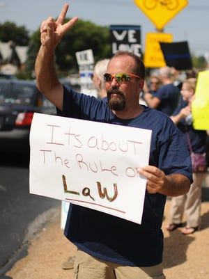 Protesters display signs during a rally in support of Officer Darren Wilson on Aug. 23, 2014, in St. Louis.