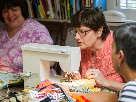 Cathy Byrnes works on a quilt with other volunteers with Quilts for Comfort at Eve English's home.