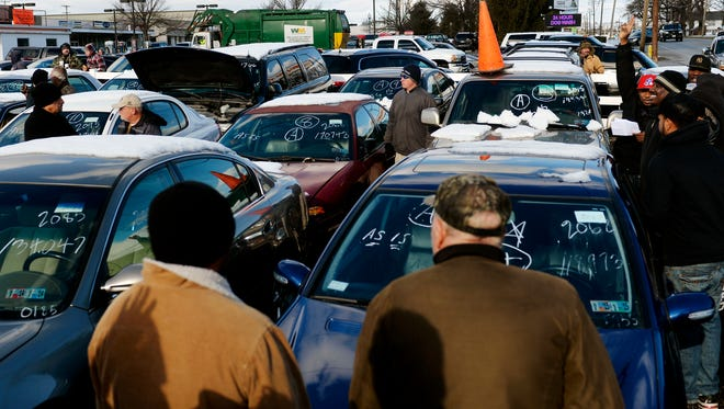 Prospective buyers gather around a vehicle up for auction, marked by the orange traffic cone, by the York County Drug Task Force in 2014, at Schaad Detective Agency. The York County Drug Task Force held its semiannual auction of 95 vehicles and about 120 items seized from alleged drug dealers. All vehicles and items are sold as-is.
