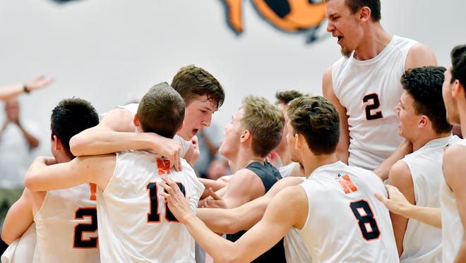 Northeastern players celebrate after winning the fifth set of a YAIAA boys' volleyball match Thursday, May 10, 2018, at Northeastern. Northeastern defeated Central 3-2 (20-25, 21-25, 25-16, 25-14, 15-7) to win the regular-season YAIAA title.