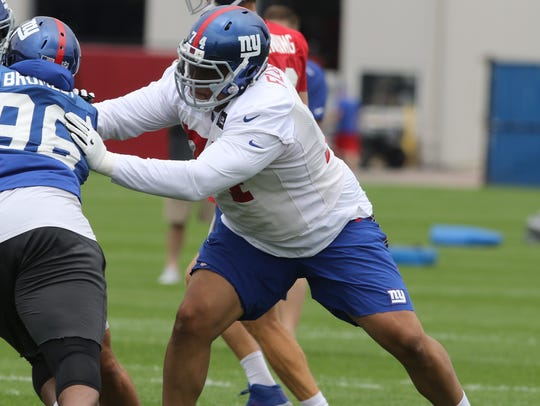 Giants tackle Ereck Flowers, facing, during training