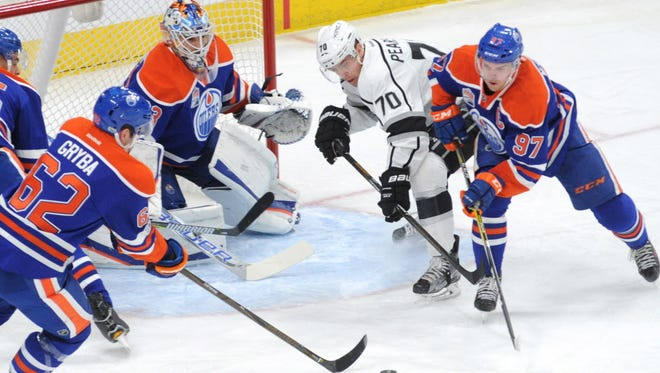Edmonton Oilers goalie Cam Talbot (33) eyes the puck while Los Angeles Kings left winger Tanner Pearson (70) battles with Oilers center Connor McDavid (97) during the first period.