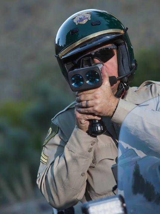 Policeman Monitoring Speed Through Radar While Sitting On Bike