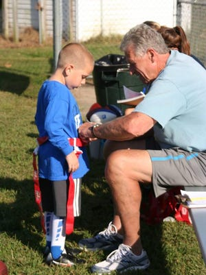 """Tom Brown works with a camper during a Rookie League session at the """"Field of Dreams"""" in his own backyard."""