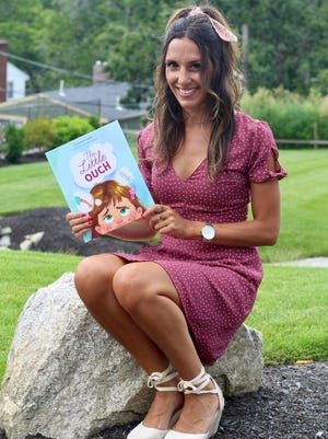 """Arlington elementary school teacher and Medford resident Katherine Picarde with her debut book, """"The Little Ouch."""""""
