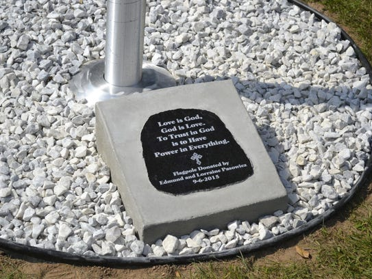 A dedication plaque sits at the base of the new flagpole