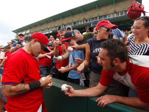 St. Louis Cardinals catcher Yadier Molina signs autographs for fans at Hammons Field after taking batting practice with the Springfield Cardinals as part of his rehab on Tuesday, August 26, 2014.