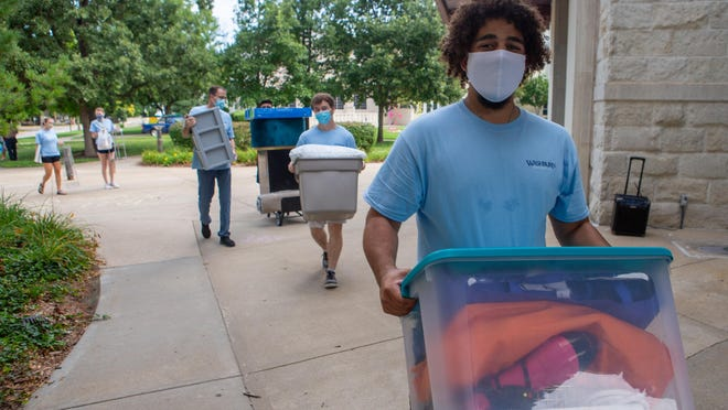 Charles Dilliehunt, a junior studying social work at Washburn, leads other move-in crew helpers as students arrived Tuesday with their belongings to the Living Learning Center at Washburn University.
