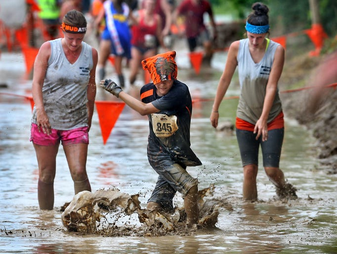 A youngster tries to get his footing walking through the flooded mud pit at the 2014 Mudathlon at White River Paintball Adventures in Anderson on Saturday, June 28, 2014. Other highlights included a 75-foot slide into a pool of mud, a cargo net crawl and muddy slope climbs.
