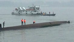 Rescue workers stand on the capsized ship in the Yangtze