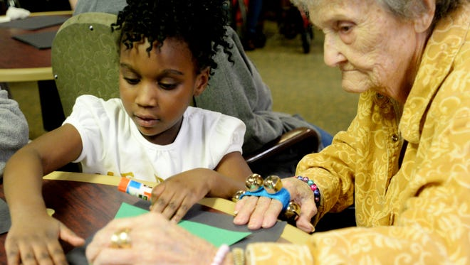 Walnut Hill pre-K student London Nettles helps Southern Hills Healthcare resident Olethia Bardue make a paper Christmas tree.
