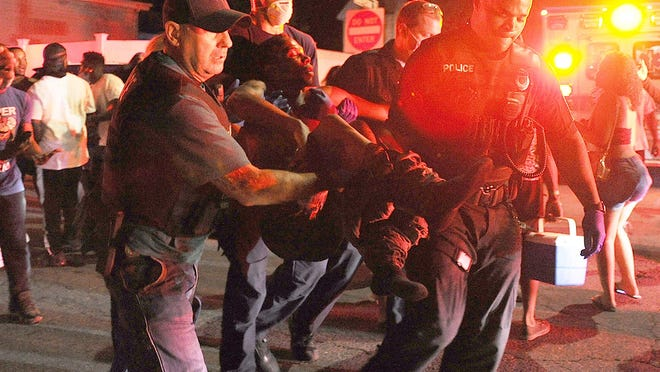 """FILE - In this Aug. 8, 2020, photo, police and firefighters can be seen carrying shooting victim Rashad """"Rudy"""" Francois outside a house party on Laureston Street in Brockton, where a woman was stabbed and five men were shot."""