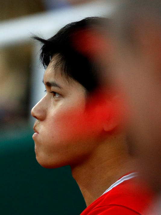 Los Angeles Angels' Shohei Ohtani watches from the dugout during the first inning of the team's baseball game against the Kansas City Royals on Thursday, April 12, 2018, in Kansas City, Mo. (AP Photo/Charlie Riedel)