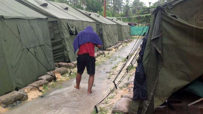 This file undated photo obtained from the Refugee Action Coalition on Feb. 18, 2014 shows a man walking between tents at Australia's regional processing centre on Manus Island in Papua New Guinea.