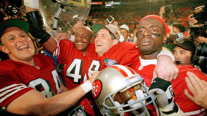 San Francisco 49ers, from left, Brent Jones, William Floyd, Steve Young and Merton Hanks, celebrate after Super Bowl XXIX on Jan. 29, 1995. Hanks was recently hired by the Pac-12 to head up its college football operations.