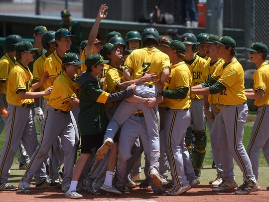 Bishop Manogue's Calvin Bailey (7) gets greeted at home plate by his teammates after hitting a home run on the first pitch of the game while taking on Basic High School (Las Vegas) during the NIAA State Baseball Championships in Reno on May 18, 2018.