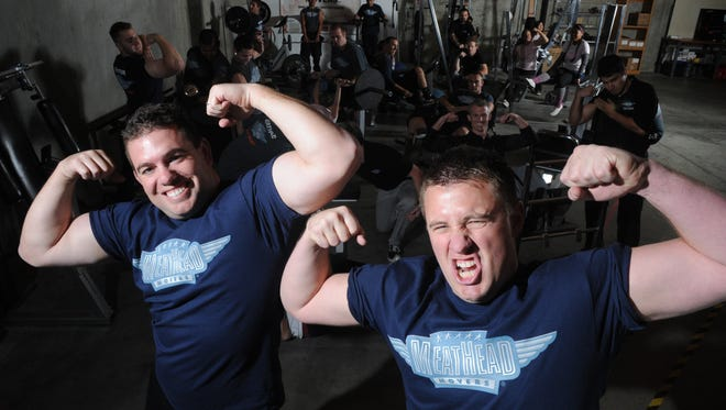 Aaron Steed, left and his brother, Evan, who lead Meathead Movers, pose in this 2011 photo with employees in their Camarillo office's gym.