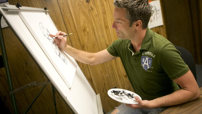 Michael Plummer Jr. works on a self-portrait Monday at Portage House, a home for men on probation or parole, in Stevens Point. His art supplies were donated by the Q Gallery Cooperative.
