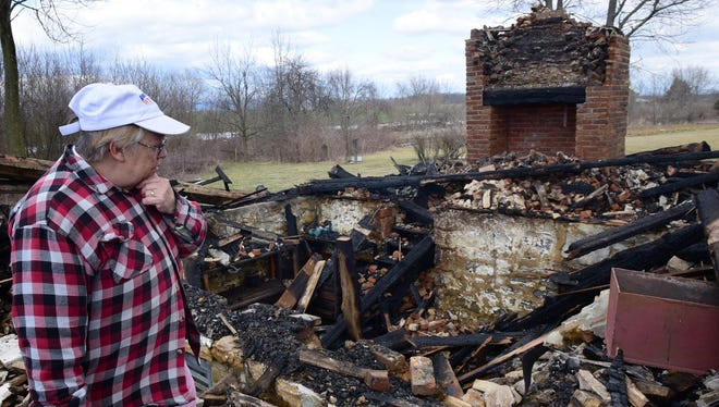 Mary Hartman, who lives in a house on the property, surveys damage to the nearly 185-year-old Negley log cabin at Conococheague Institute Monday, Feb. 29. 2016 following an early morning fire.